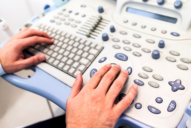 Close up view at doctors hands working on ultrasounds keyboard