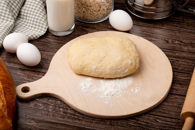 Close-up view of dough and flour on cutting board with eggs on wooden background