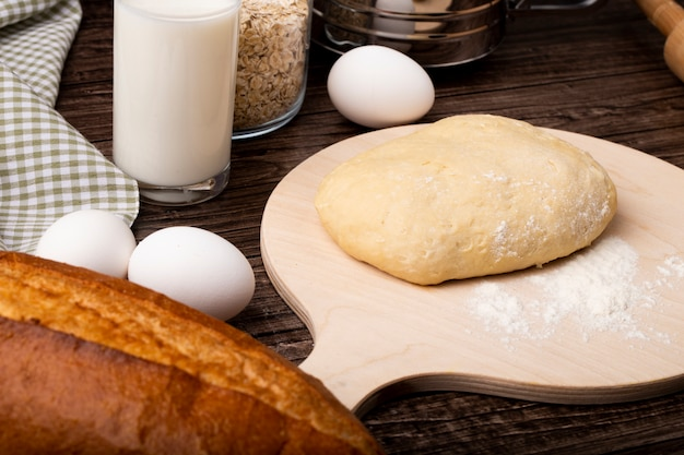 Close-up view of dough with flour on cutting board and eggs milk on wooden background
