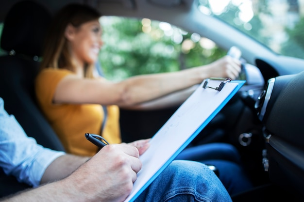 Close up view of driving instructor holding checklist while in background female student steering and driving car