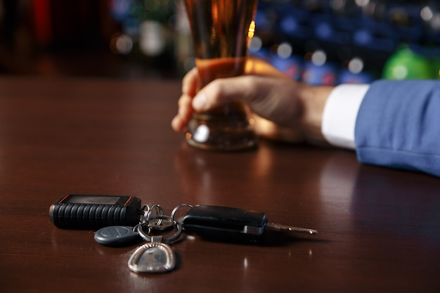 Close up view of drunk man giving car key to woman, on blurred background. don't drink and drive concept