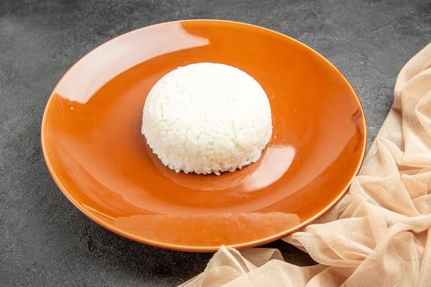 Vista ravvicinata del pasto di riso facile-preparato su un piatto marrone e un asciugamano sul nero