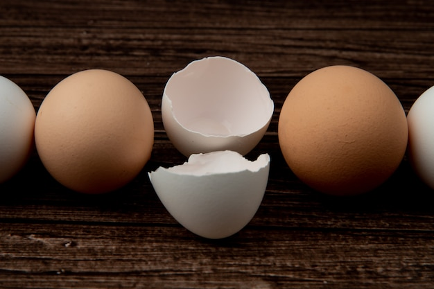 Close-up view of eggshell and eggs on wooden background