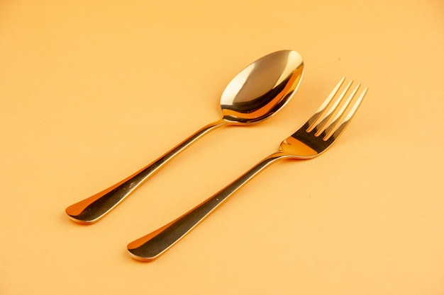 Close up view of elegant shiny golden stainless spoon and fork on isolated yellow background with free space