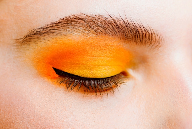 Close-up view of eye with yellow and orance make-up