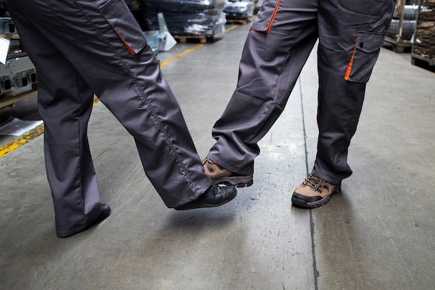 Close up view of factory workers touching with legs and greeting due to corona virus and infection