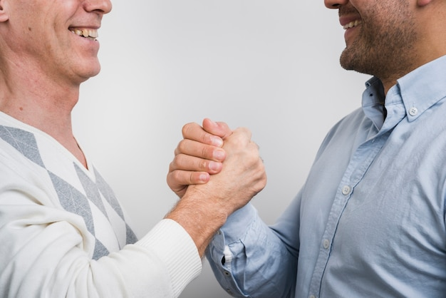 Close-up view of father and son holding hands