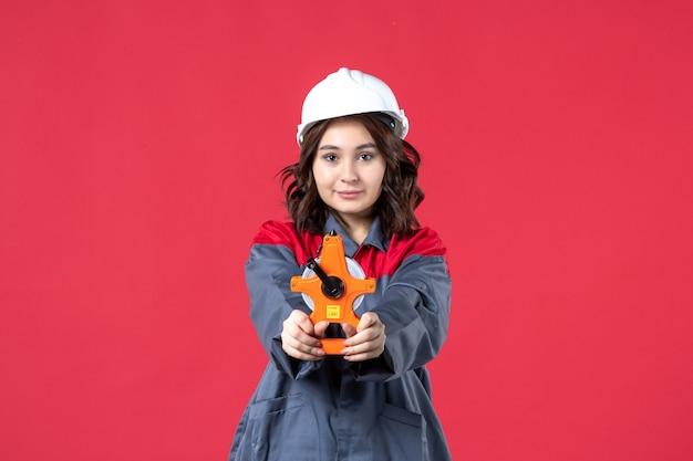 Vista ravvicinata della donna architetto in uniforme con elmetto che mostra nastro di misurazione sulla parete rossa