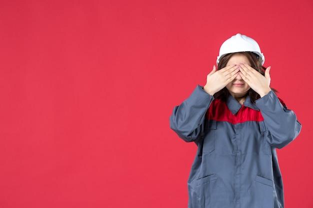Vista ravvicinata del costruttore femminile in uniforme con elmetto e chiudendo gli occhi sulla parete rossa isolata