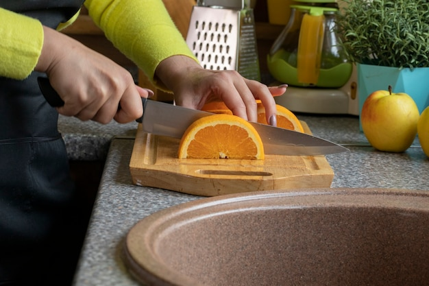 Close up view of female cook slices juicy orange on wooden board