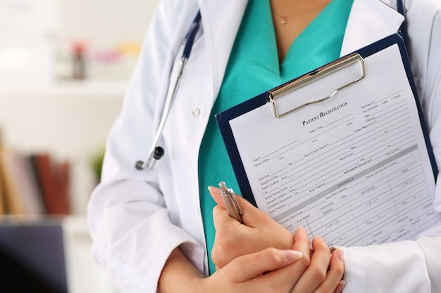 Close up view of female doctor hands holding clipping pad with patient registration form