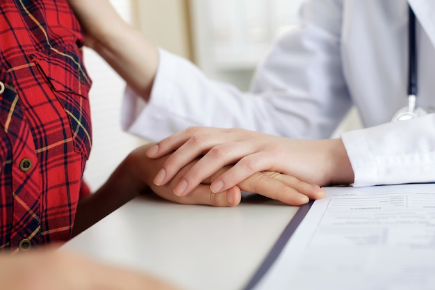 Close up view of female doctor touching patient hand for encouragement, empathy, cheering, support after medical examination