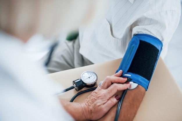 ビューを閉じます。女医は眼圧計を使って年配の男性の血圧を測定します。