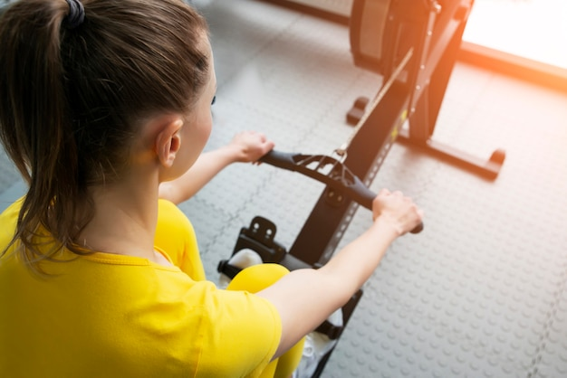 Close up view of female fitness instructor uses a rowing machine