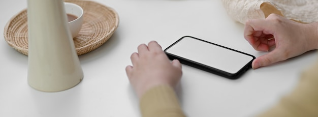 Close up view of female freelancer using mock-up smartphone to relax