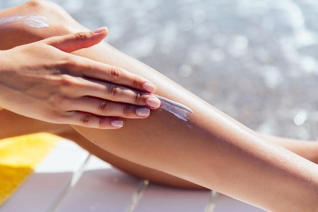 Punto di vista del primo piano della mano femminile che applica protezione solare sulla sua gamba, vicino al mare.