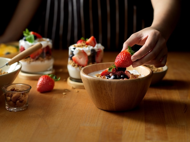 Close up view of female hand decorating strawberry on a bowl of granola with greek yogurt and berries