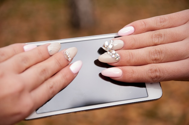 Close up view of female hand with long nails typing text message outdoors