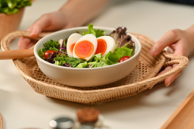 Close up view of female hands holding wicker tray with a plate salad with boiled eggs, lettuce and tomato