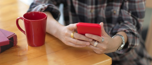 Close up view of female hands using smartphone on wooden table with coffee mug