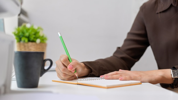 Close up view of female office worker hand writing on notebook on white desk with cup and plant pot