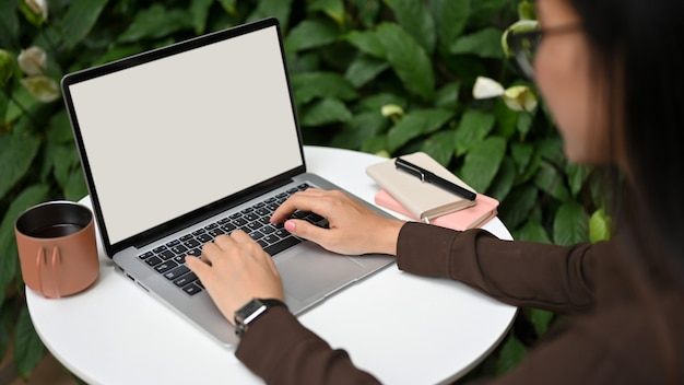 Close up view of female office worker typing on laptop keyboard on round table in garden at home