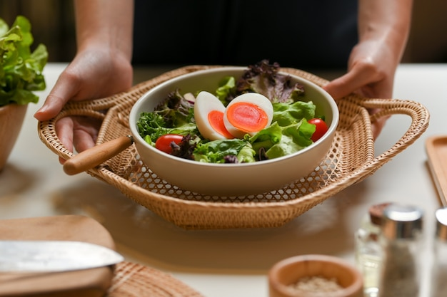 Close up view of female waitress hands serving salad with boiled eggs, lettuce and tomato in restaurant