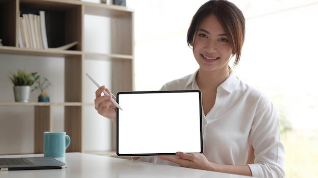Close up view of female worker showing  tablet screen while standing in office room.