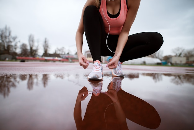 Close up view of fitness attractive woman tying her right shoe above the pond on the athletic track.