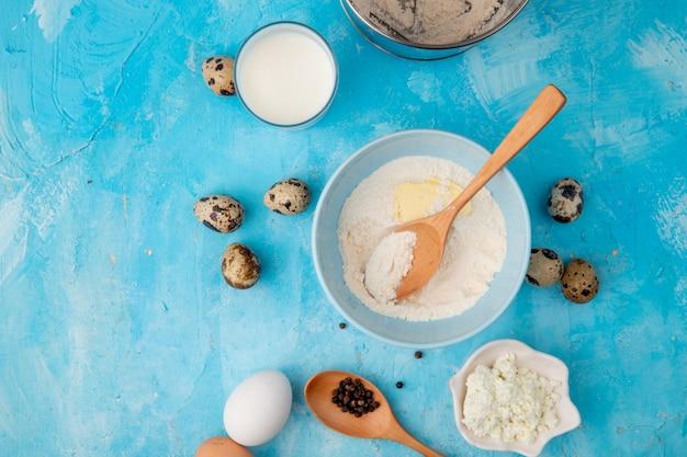 Vista del primo piano degli alimenti come uovo della ricotta della farina con latte su fondo blu con lo spazio della copia