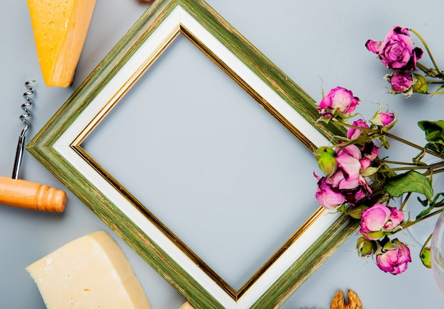 Close-up view of frame with cheese corkscrew and flowers around on white with copy space