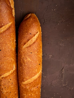 Close-up view of french baguettes on maroon background with copy space