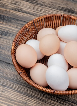 Close up view of fresh chicken eggs on a bucket on a wooden background