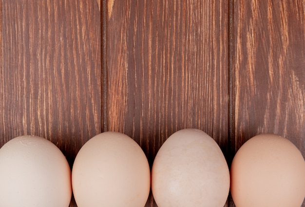 Close up view of fresh chicken eggs on a wooden background with copy space