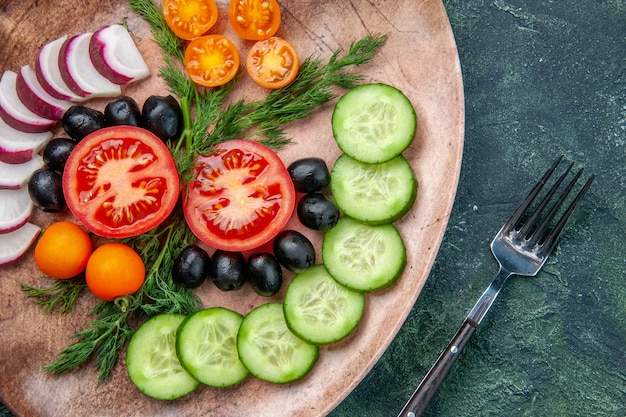 Close up view of fresh chopped vegetables olives in a brown plate and fork on green black mixed colors background