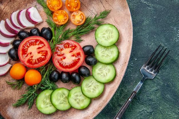 Vista ravvicinata di verdure fresche tritate olive in un piatto marrone e forchetta su sfondo verde nero colori misti