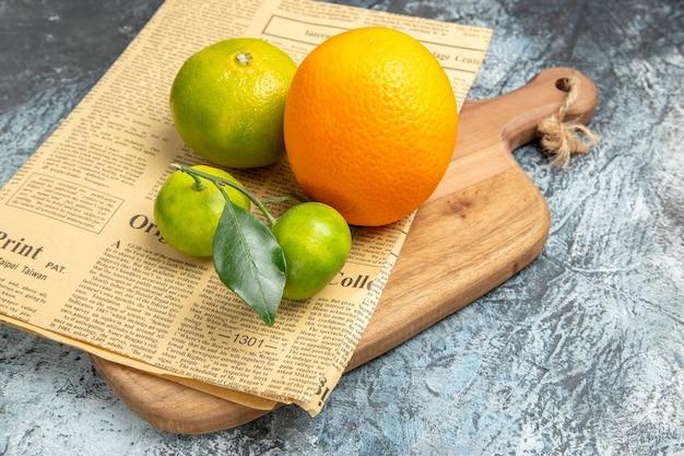 Vista ravvicinata di agrumi freschi con foglie e giornali su tagliere di legno tagliato a metà tavola grigia