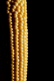 Close up view of fresh corn over black wall