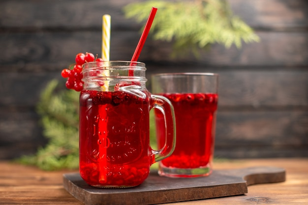 Close up view of fresh currant juice in a glass and a cup served with tube on a wooden cutting board