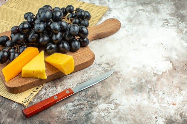 Close up view of fresh delicious black grape bunch and various kinds of cheese on wooden cutting board and knife on mixed color background
