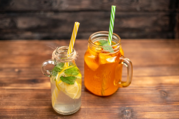 Close up view of fresh detox water and fruit juice served with tubes on a brown background