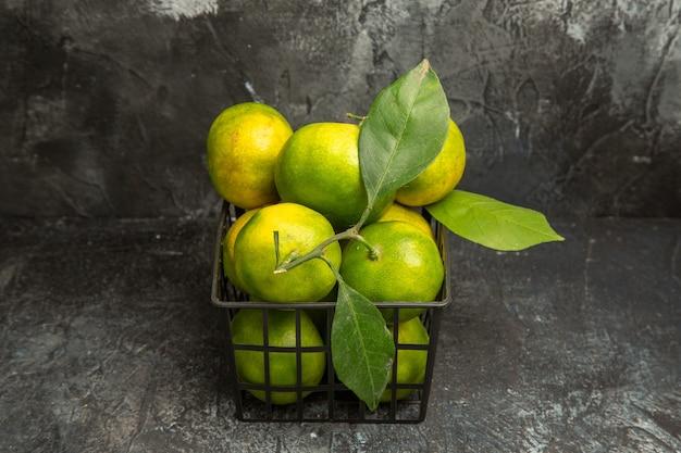 Vista ravvicinata di mandarini verdi freschi con foglie in un cesto su sfondo grigio