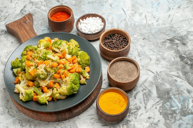 Close up view of fresh and healthy vegetable salad on wooden cutting board on white table