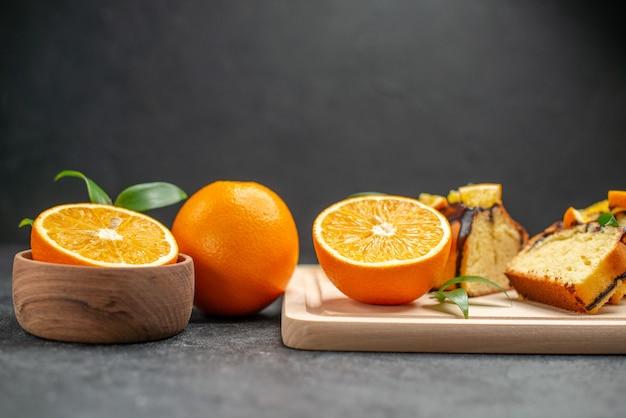 Vista ravvicinata di fette di limone fresco e fette di torta tritata appena sfornata sul tavolo scuro