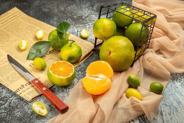 Vista ravvicinata di limoni freschi in un cesto nero caduto su un coltello per asciugamani e un giornale su un tavolo grigio