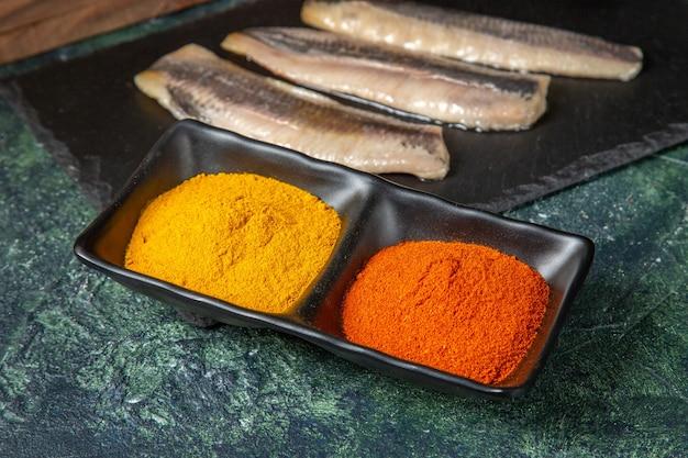 Vista ravvicinata del pesce fresco crudo tritato sulle spezie del tagliere di legno nero sulla superficie dei colori della miscela