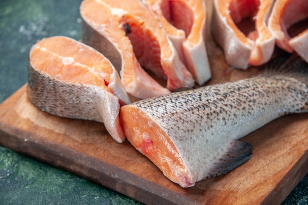 Vista ravvicinata di pesce crudo fresco sul tagliere di legno marrone sulla tabella dei colori della miscela scura con spazio libero