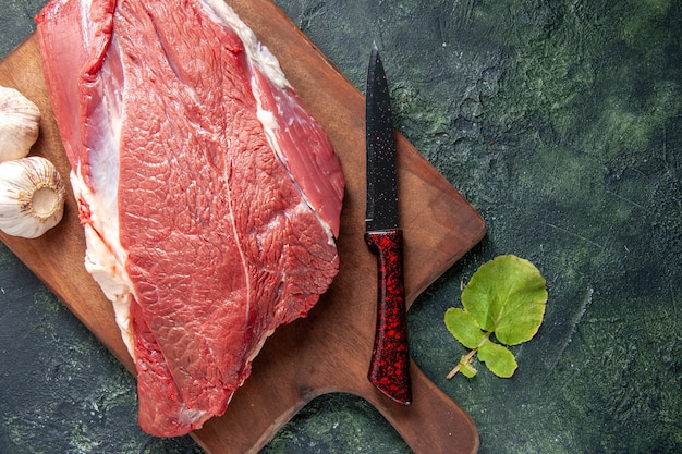Close up view of fresh raw red meats on brown wooden cutting board and knife garlics on dark color background