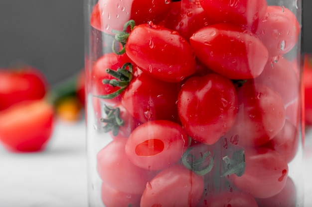 Close up view of fresh ripe wet cherry tomatoes in a glass jar