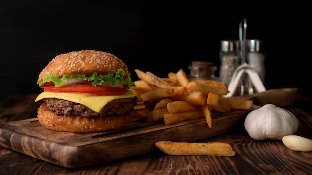 Close up view of fresh tasty beef burger and french fries on wooden tray with seasoning and garlic